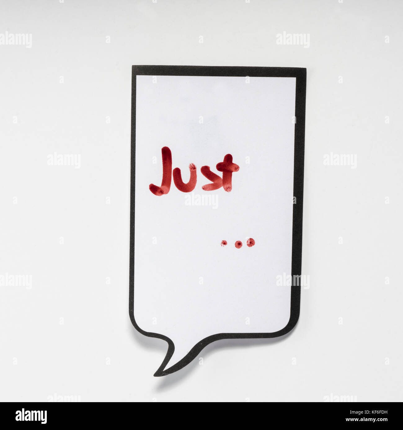 a white memo pad with the shape of a comic with the inscription 'just' - Stock Image