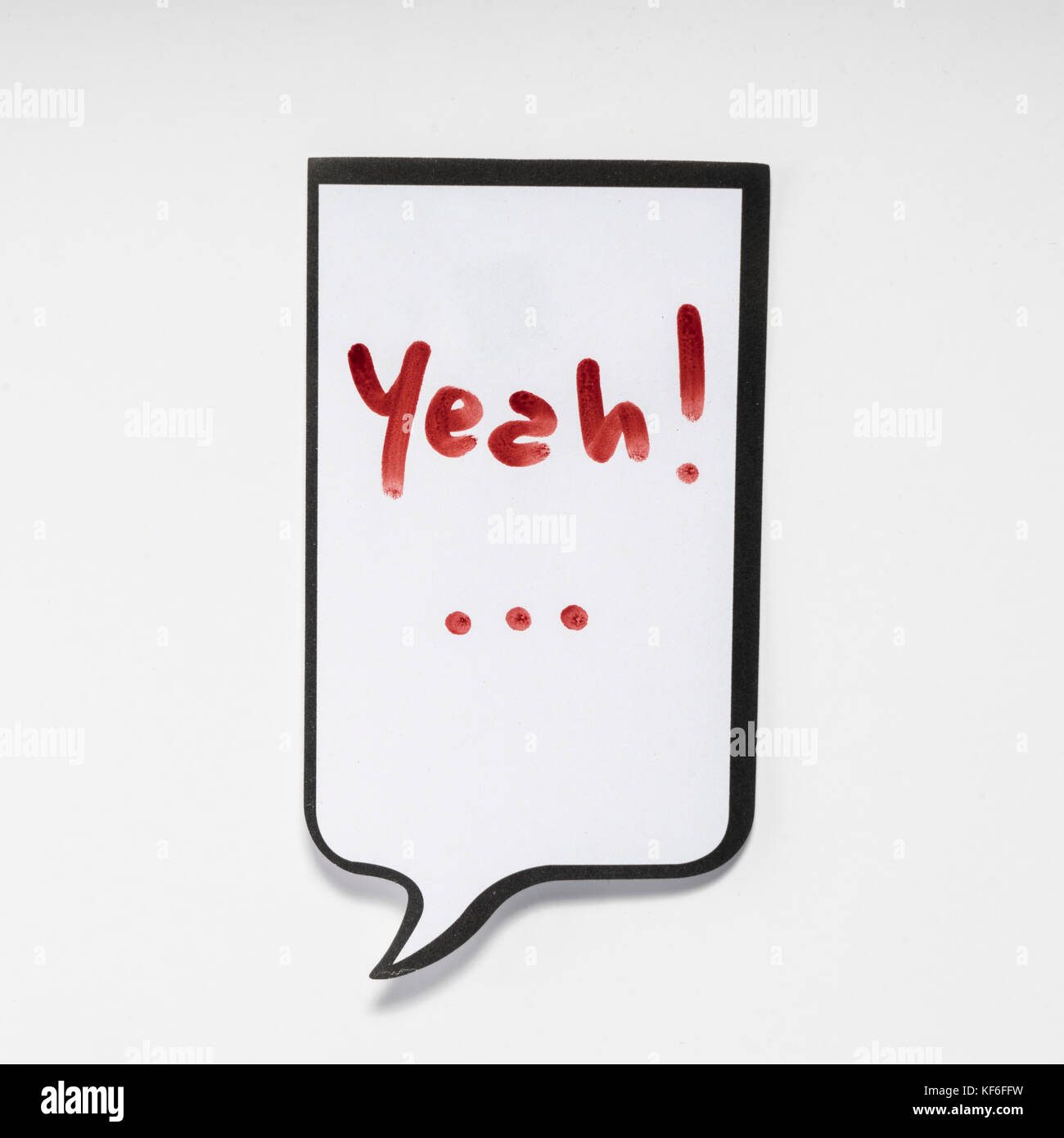 a white memo pad with the shape of a comic with the inscription 'yeah' - Stock Image