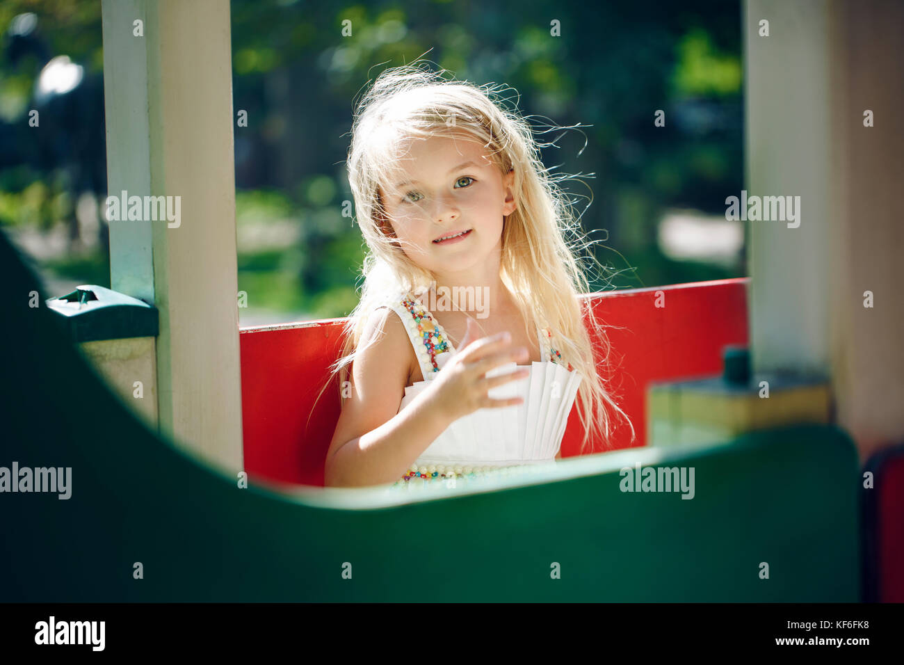 summer, childhood, leisure, gesture and people concept - happy little girl playing on children playground at sunny - Stock Image