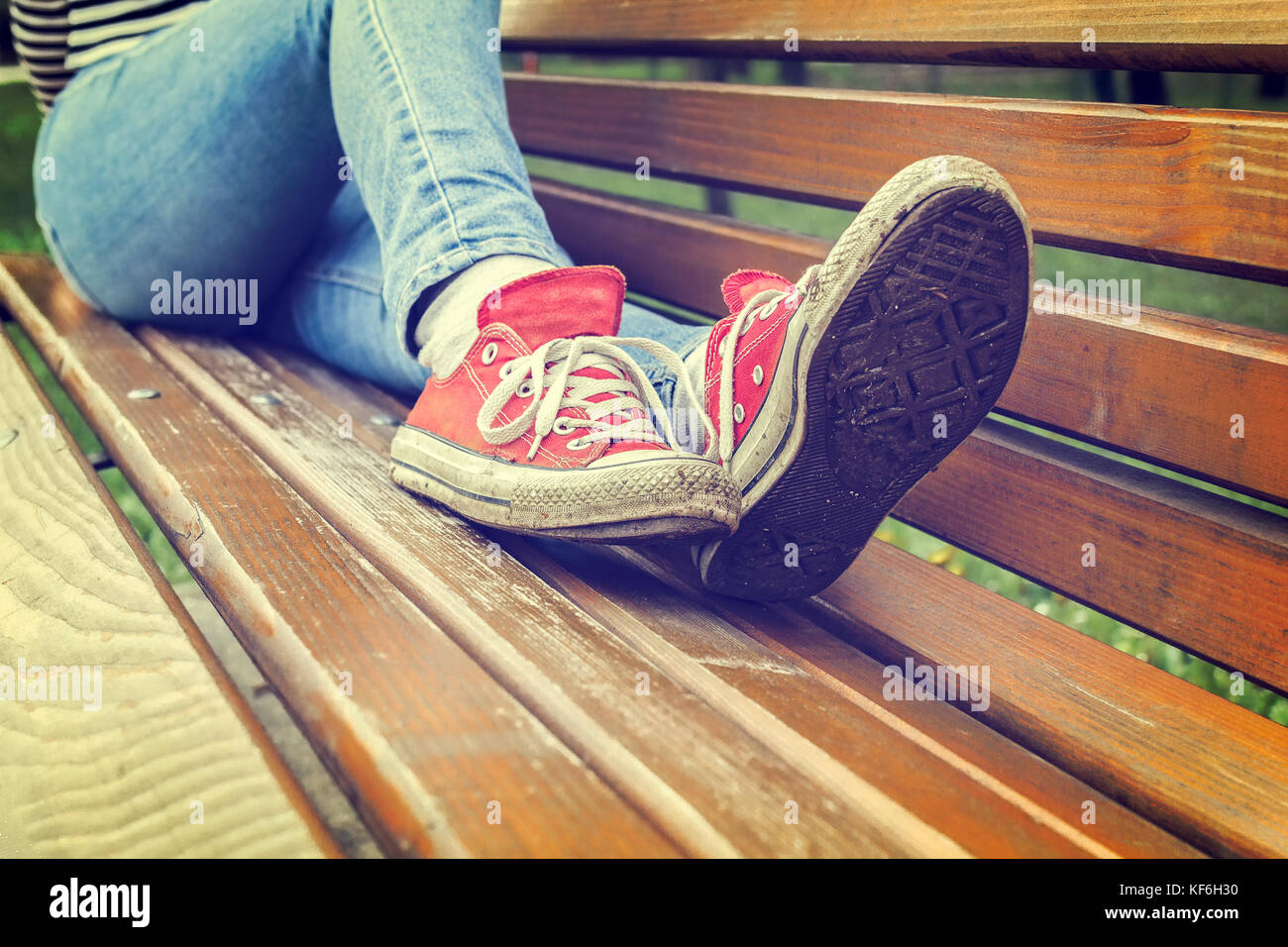 Woman's legs wearing red canvas sneakers and blue jeans, on a park bench, retro styled photo - Stock Image