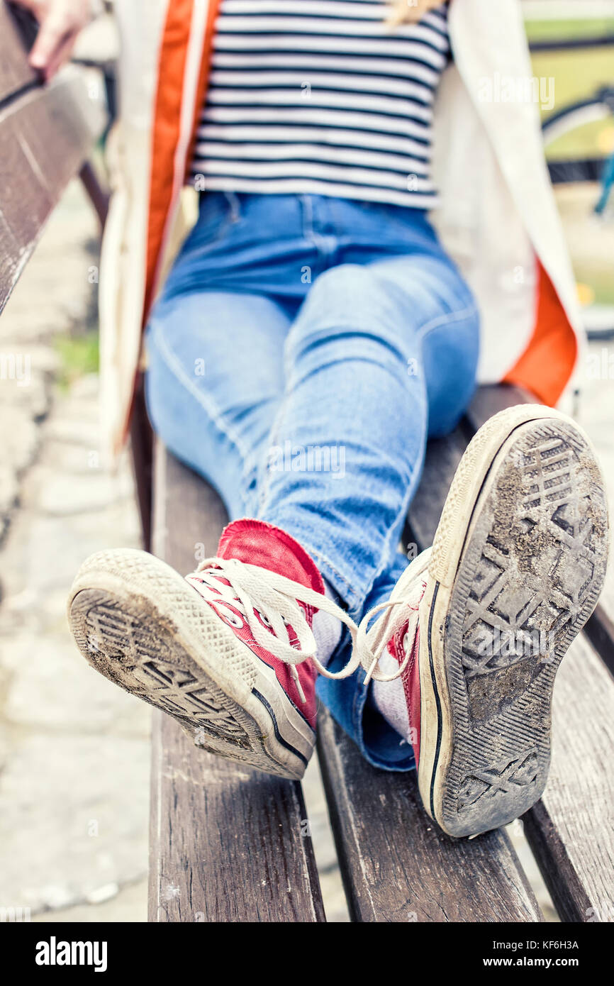 Woman's legs wearing red canvas sneakers and blue jeans, sitting on a bench - Stock Image