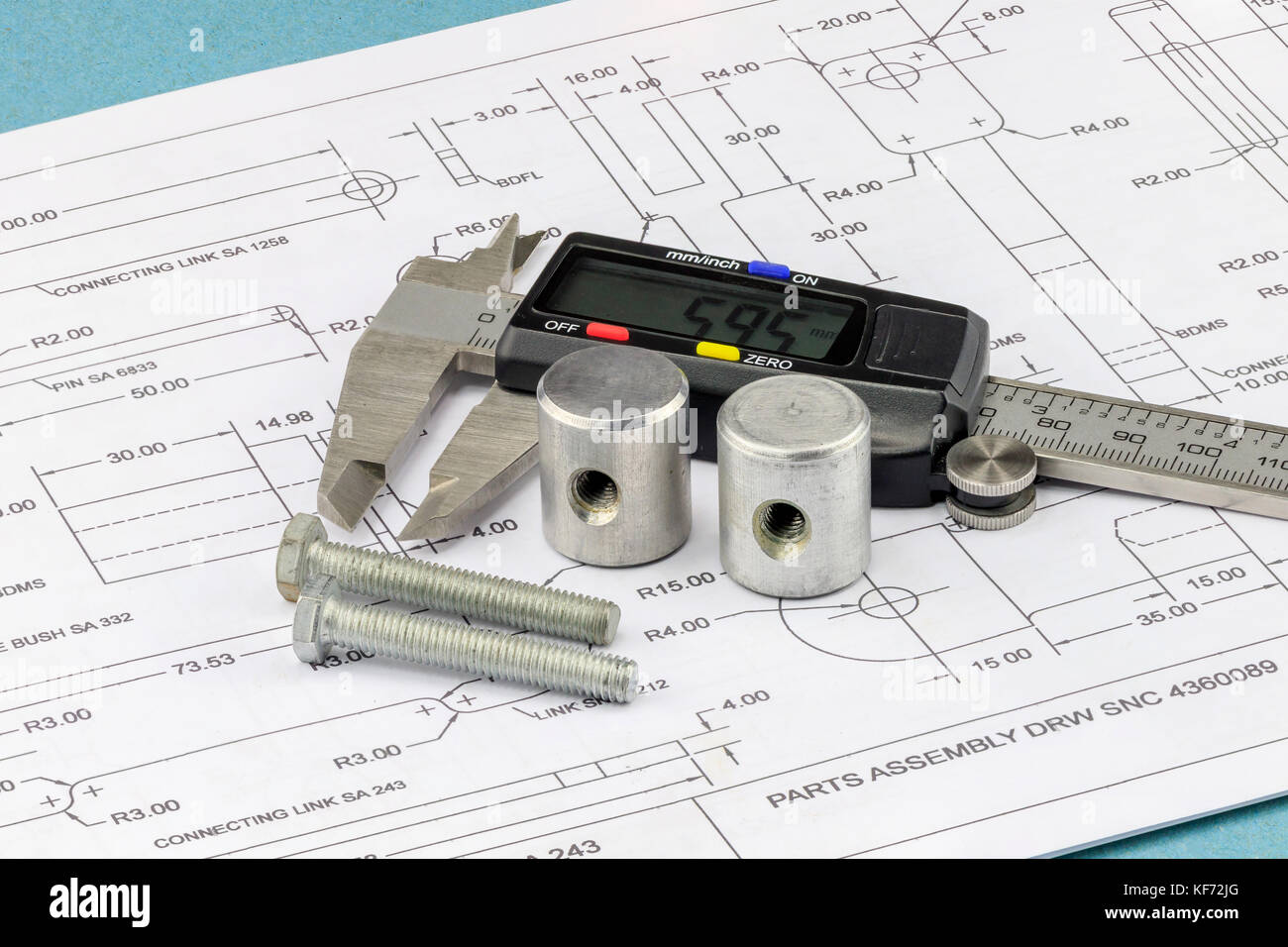 Vernier Callipers, bolts and parts placed on an engineering drawing - Stock Image