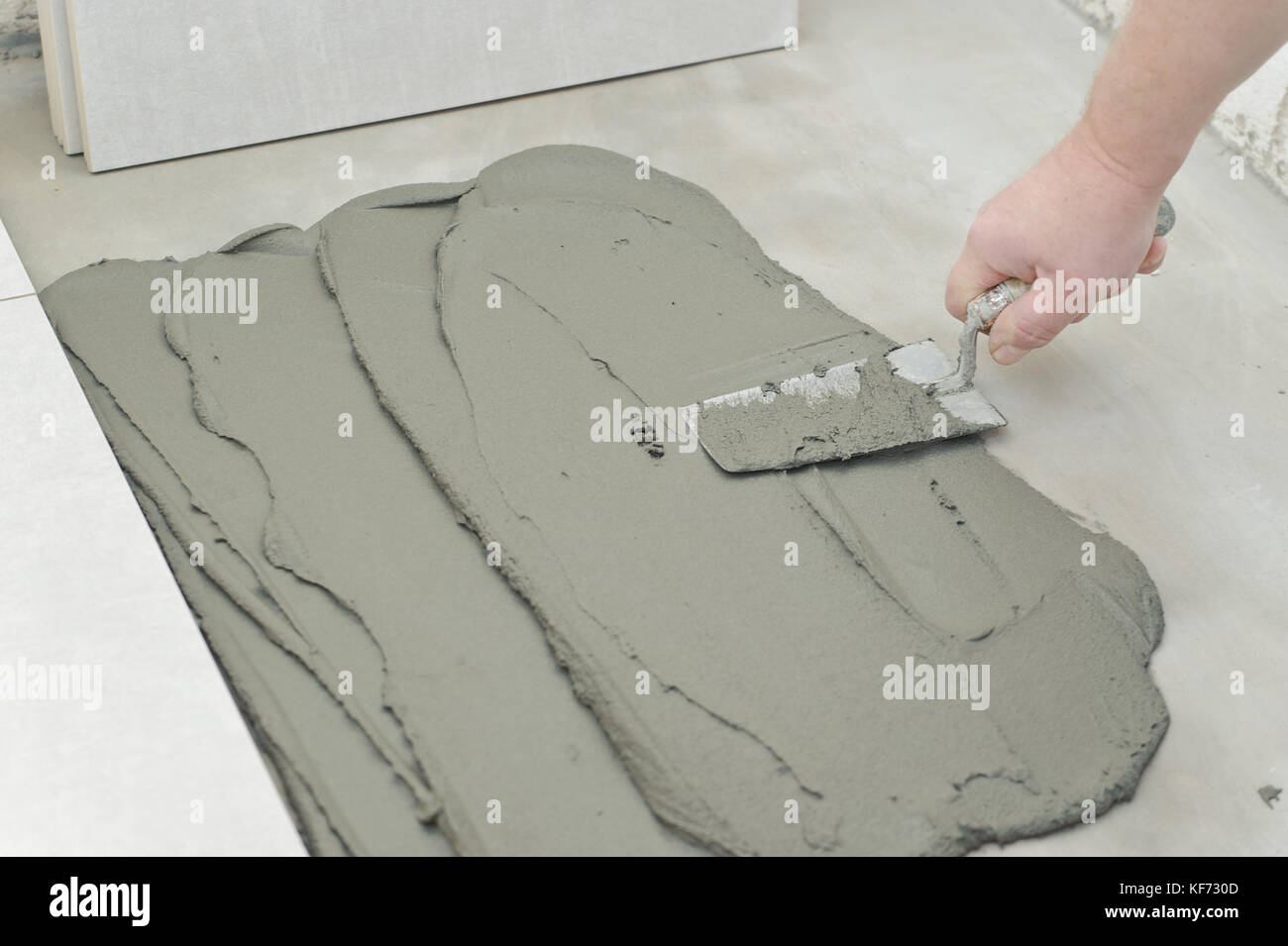 Laying Ceramic Tiles. Troweling mortar onto a concrete floor in ...