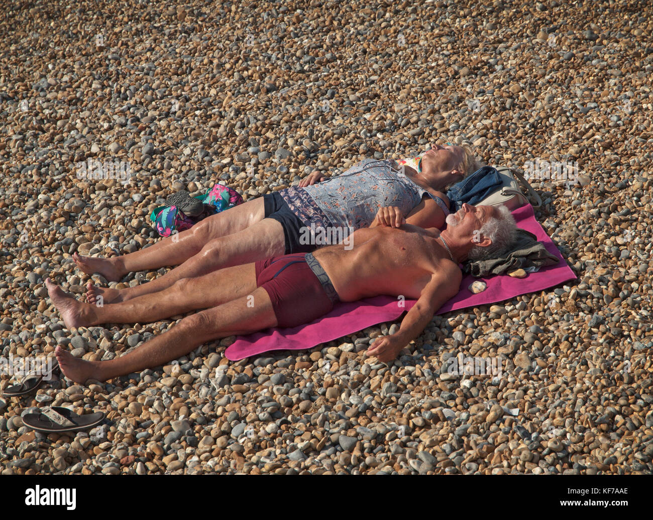 A middle aged couple sunbathe on the pebbles of Brighton beach - Stock Image