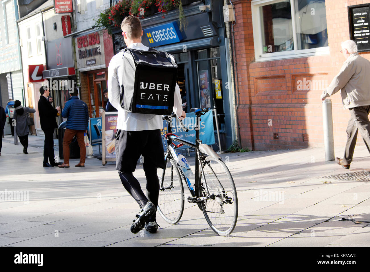 Young man walking with bicycle and UBER EATS (Ubereats) food delivery rucksack back view Cardiff City Centre Wales - Stock Image