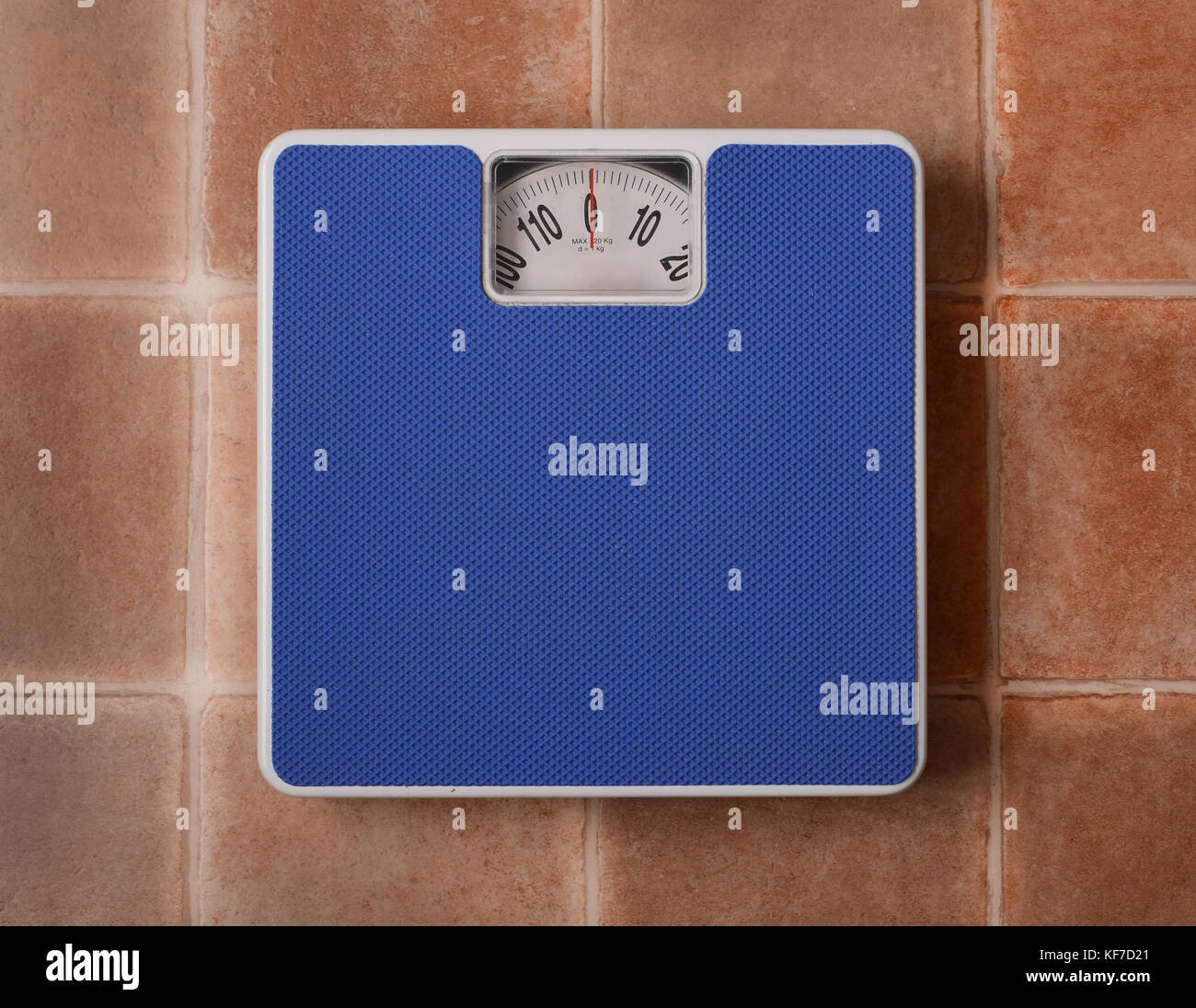 Bathroom scale isolated on terracotta floor background - closeup - Stock Image
