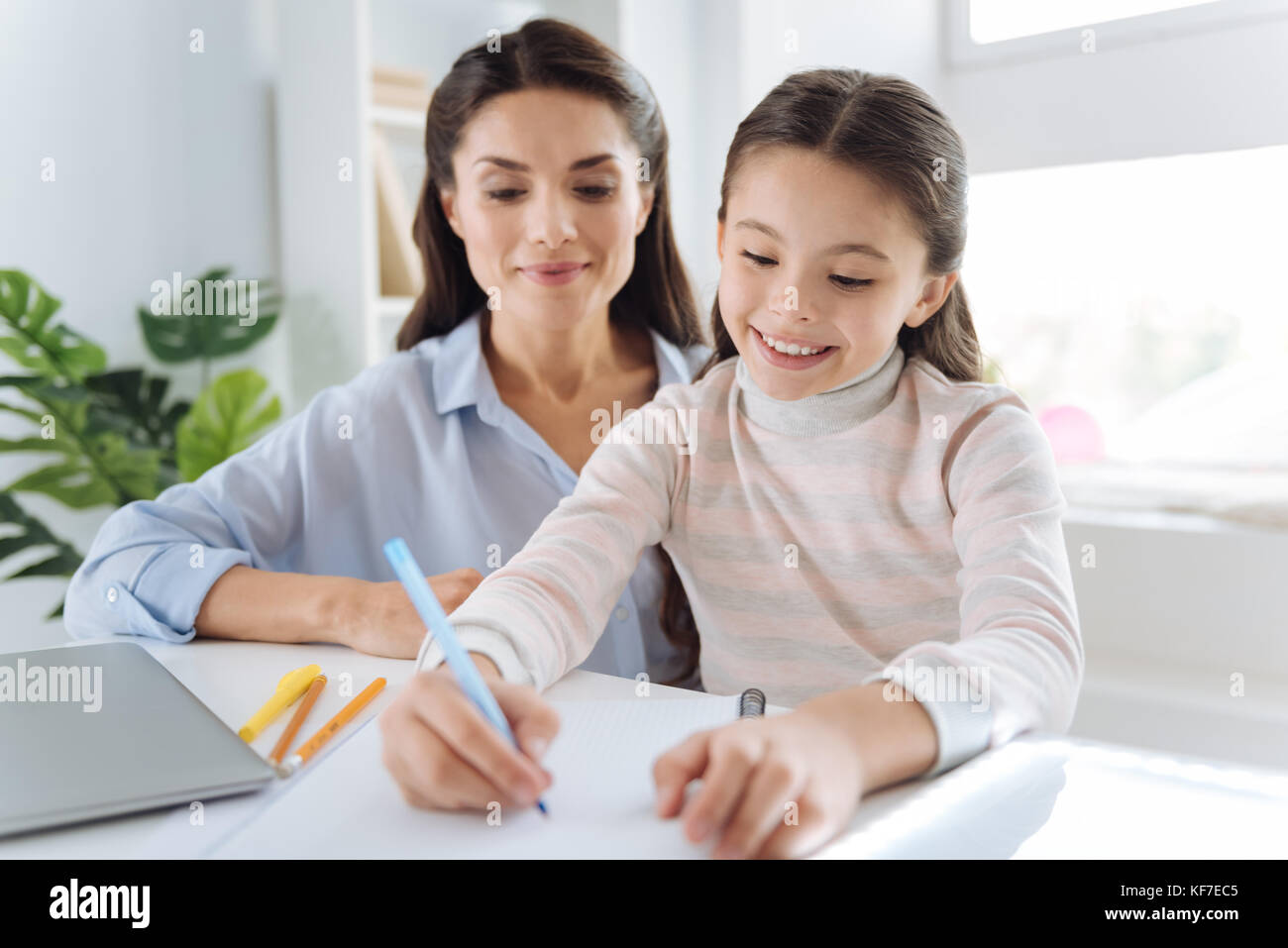 Cute intelligent girl taking notes - Stock Image