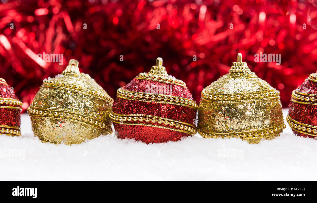 red and gold christmas balls in snow with tinsel christmas background KF7ECJ