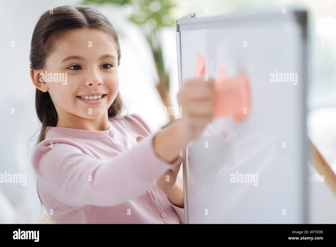 Happy cheerful girl holding a sticky note - Stock Image
