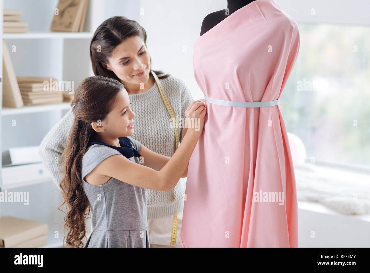 Positive cute girl learning clothes design - Stock Image