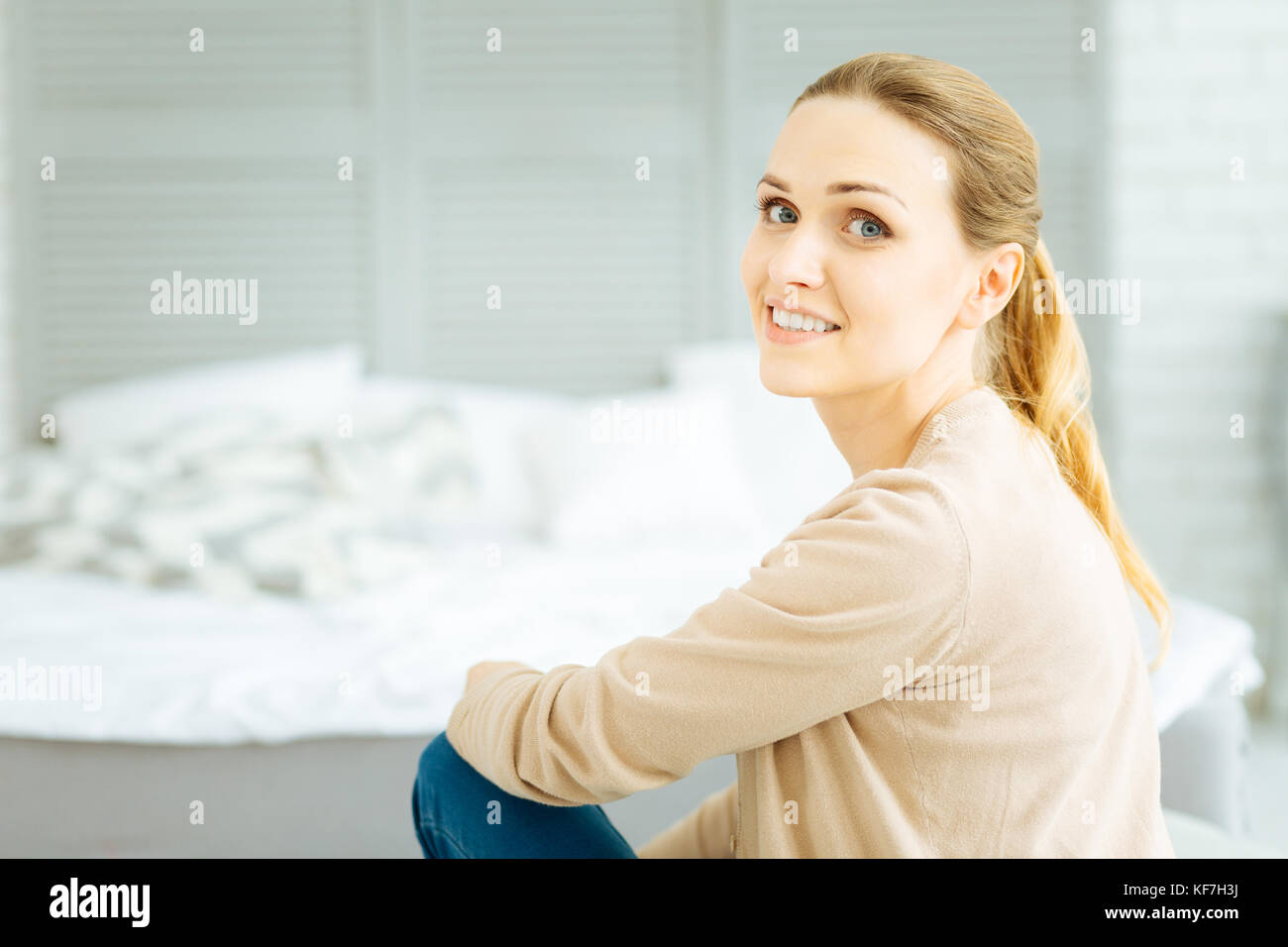 Cheerful calm woman sitting on a comfortable bed - Stock Image