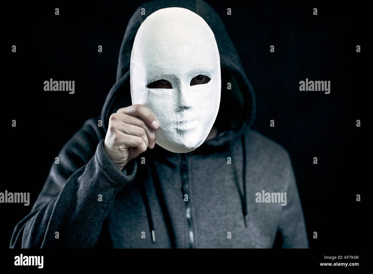 Man holding white mask for hide his face Stock Photo