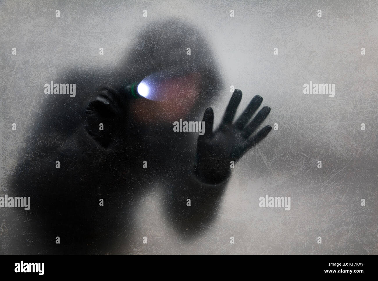 Thief with flashlight behind a dusty scratched glass - Stock Image