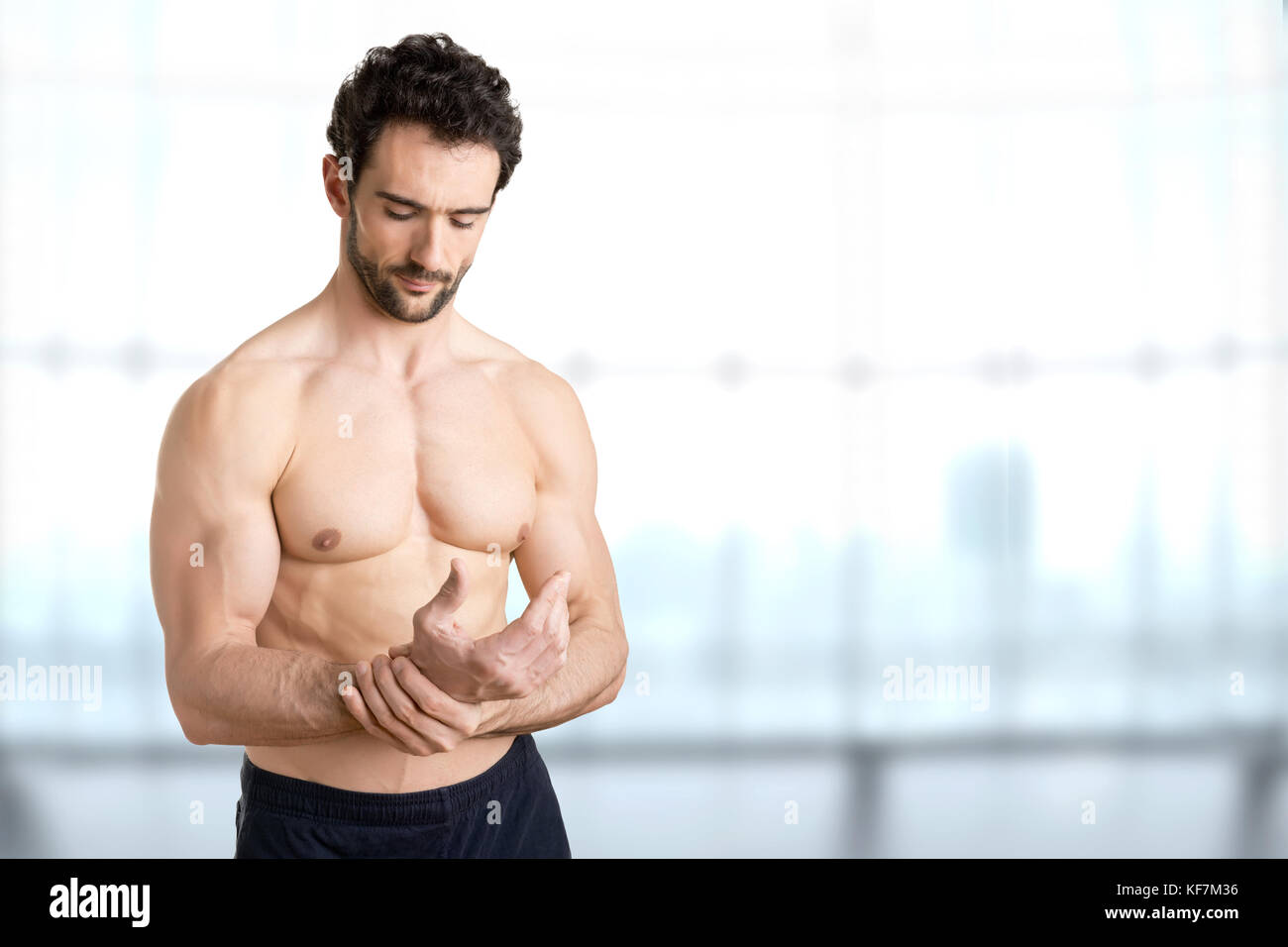 Male with pain in his wrist, in a blue background - Stock Image