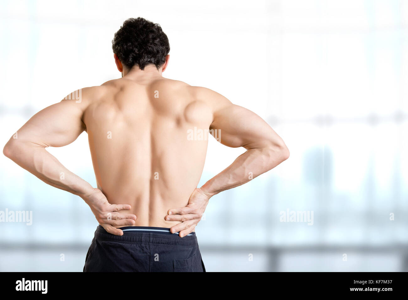 Male athlete with pain in his lower back, isolated in white. Red spot around painful area. - Stock Image