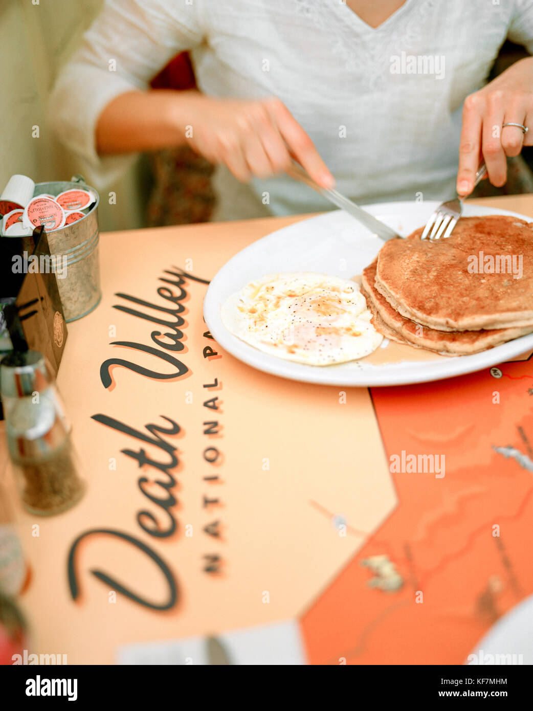 USA, California, Death Valley, woman having breakfast, 49er Cafe, midsection - Stock Image