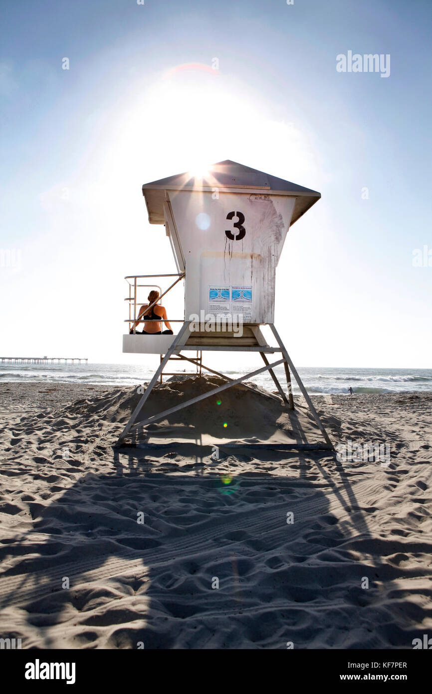 USA, California, San Diego, a woman watches the waves come from on top of lifeguard Tower 3 along Ocean Beach - Stock Image