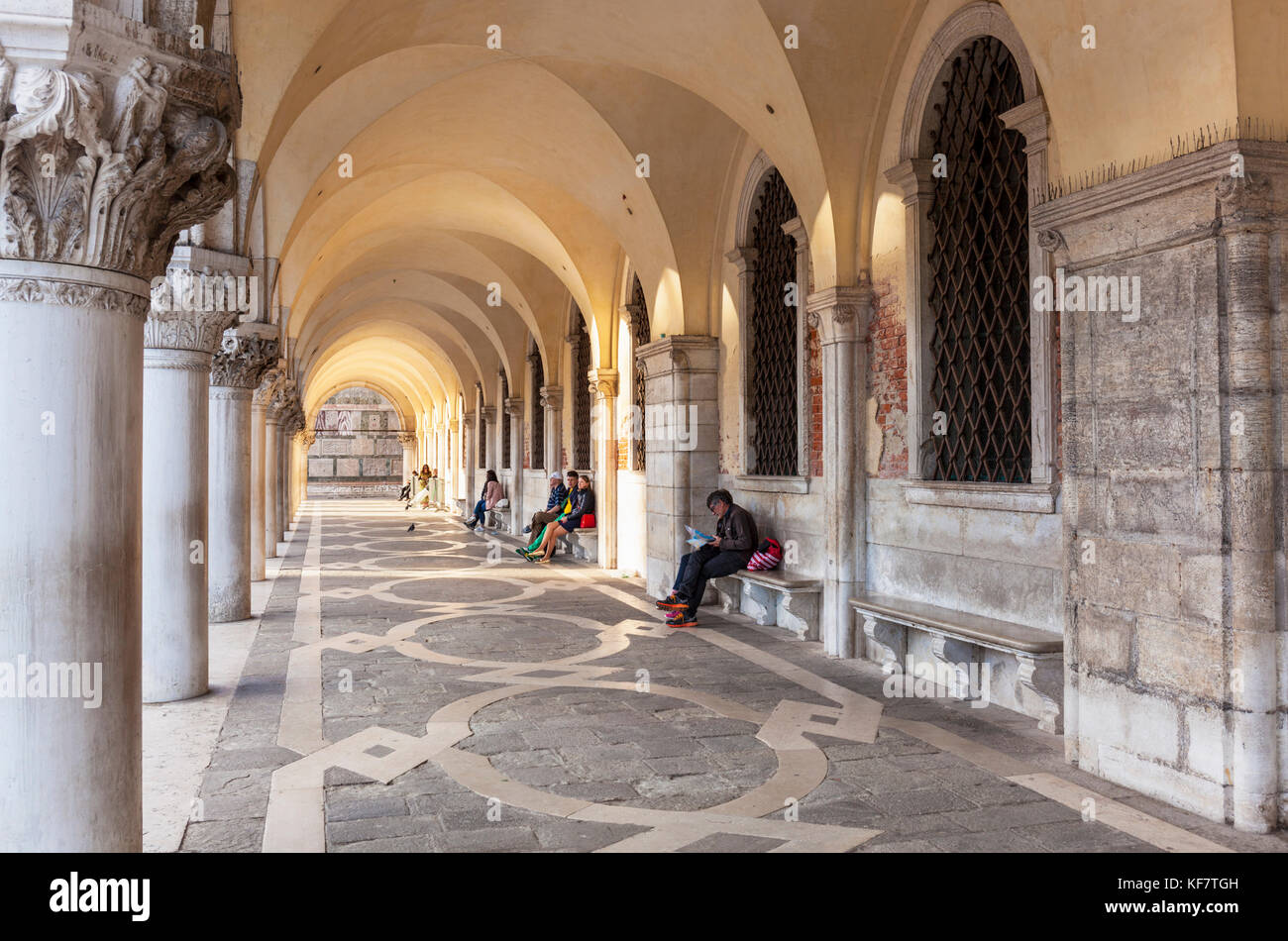 VENICE ITALY VENICE People sat under the arches in the Archway Portico of the Doges Palace Palazzo Ducale St marks - Stock Image