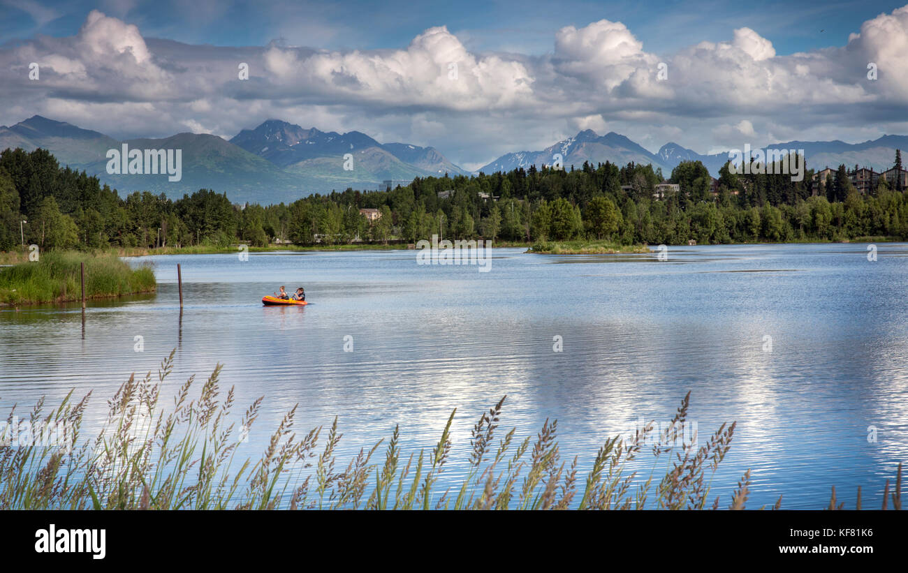 USA, Alaska, Anchorage, two individuals float in a raft in the lake within Waterfront Park - Stock Image