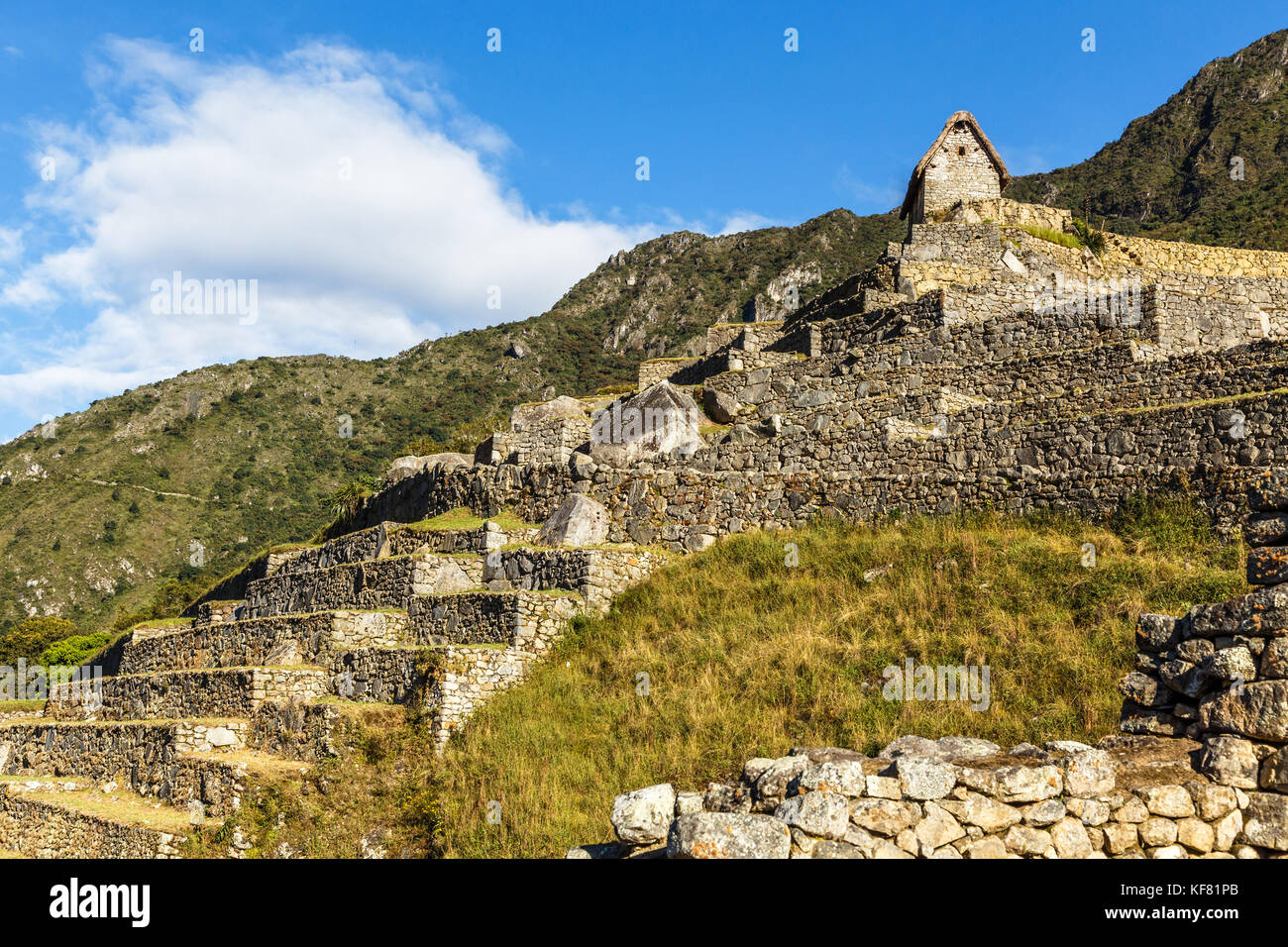 Machu Picchu green terraces and ruins with mountains in the background, Urubamba provnce, Peru - Stock Image