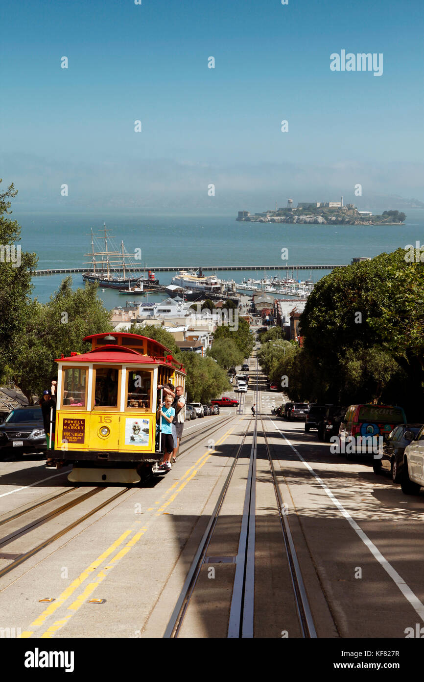 USA, California, San Francisco, a trolly drives up Hyde street with the San Francisco Bay and Alcatraz in the distance - Stock Image