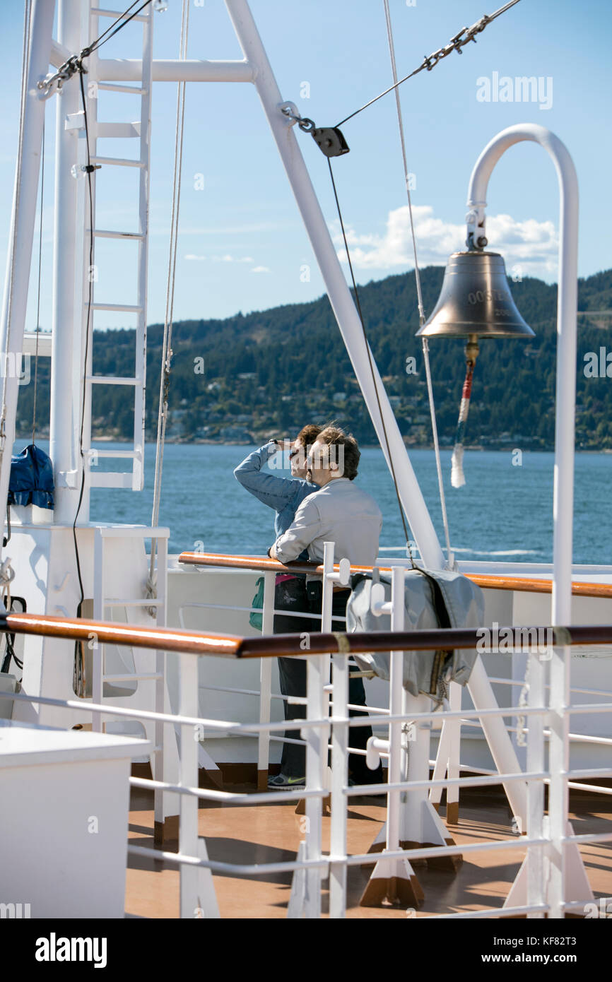 CANADA, Vancouver BC, a couple takes in the scenery off the Holland America cruise ship, the Oosterdam, as it leaves Stock Photo