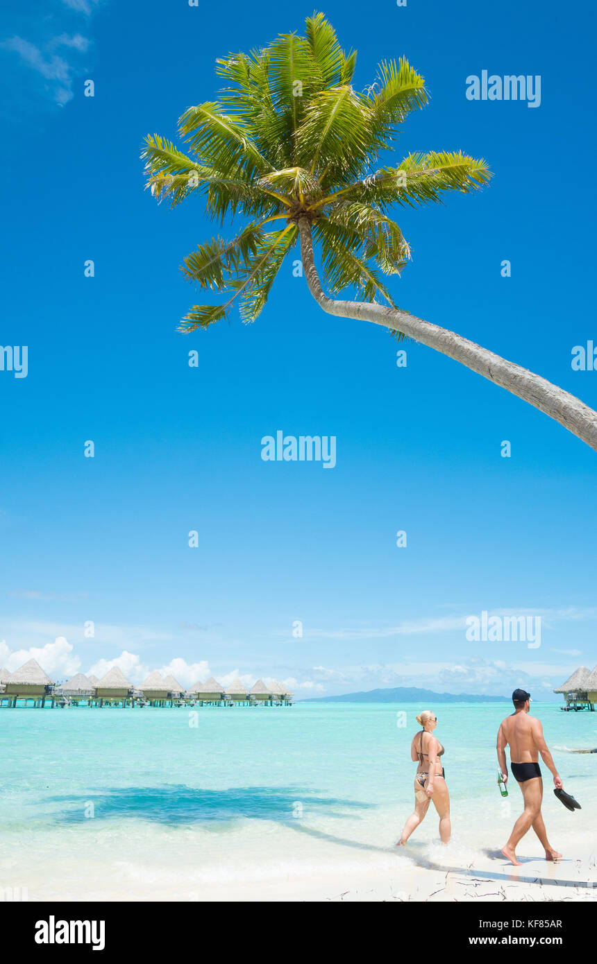 Two guests take a walk along the beach at the Intercontinental Le Moana resort in Bora Bora, French Polynesia - Stock Image