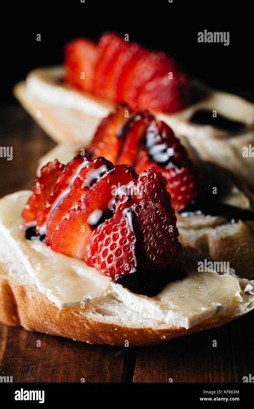 Canapes with brie cheese, fresh strawberries on rustic wooden surface - Stock Image
