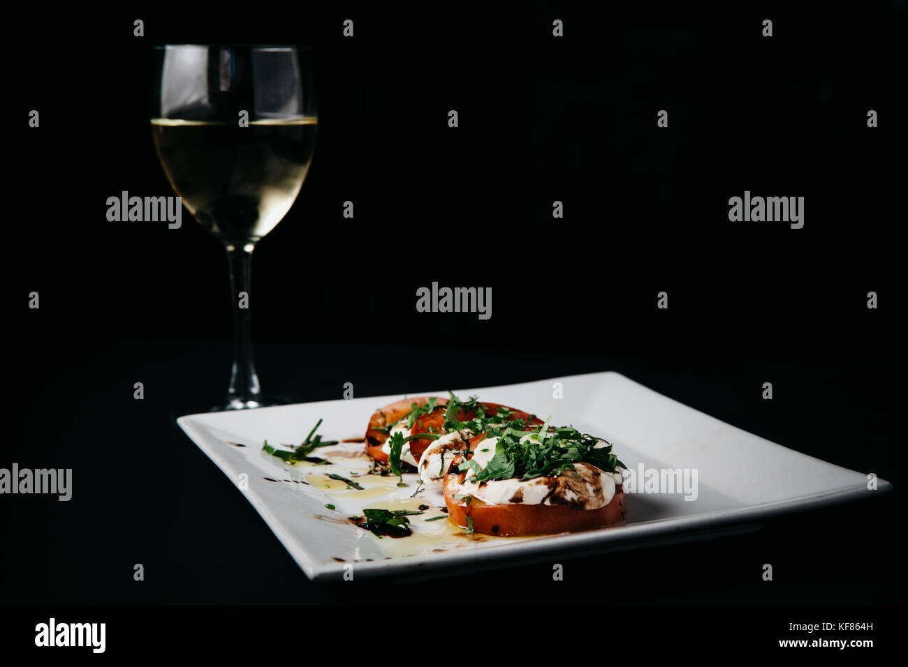 Fresh italian caprese salad with mozzarella cheese, tomatoes and basil on a white plate and black background - Stock Image