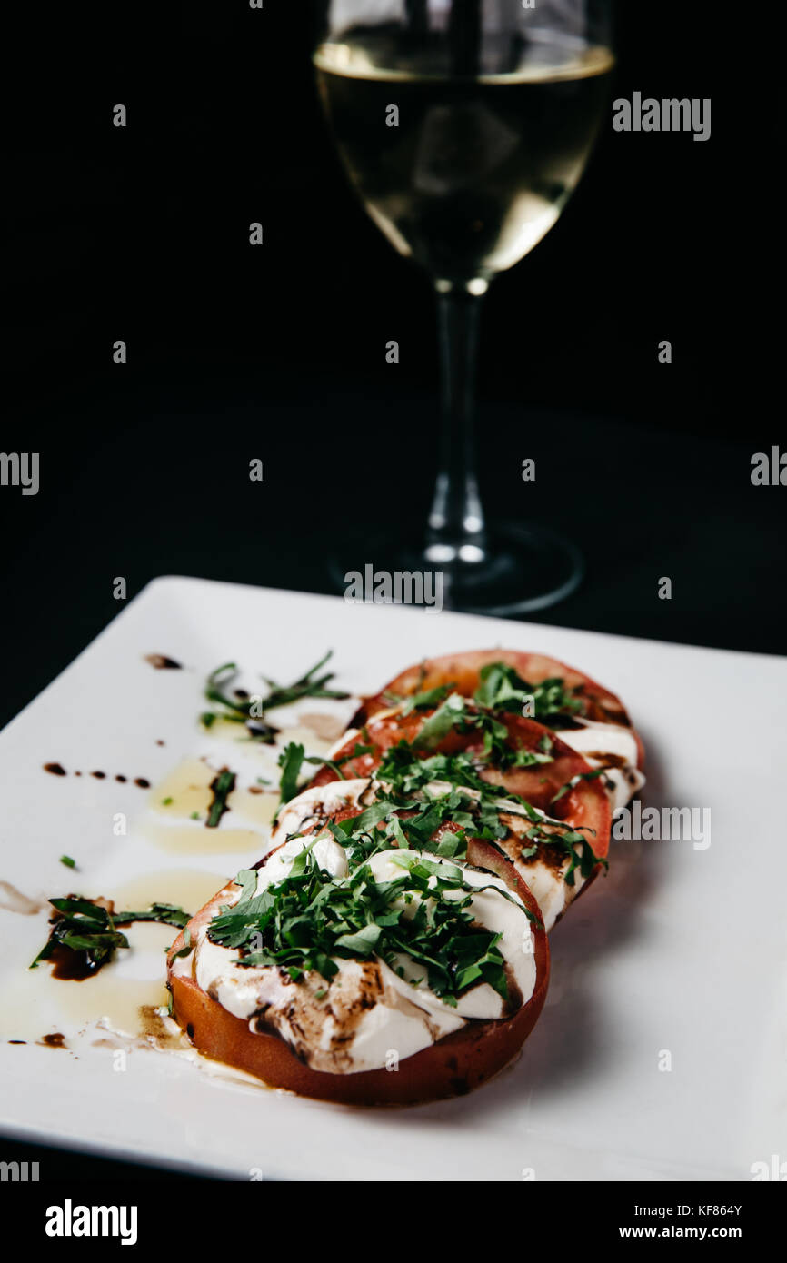 Fresh italian caprese salad with mozzarella cheese, tomatoes and basil on a white plate and black background Stock Photo