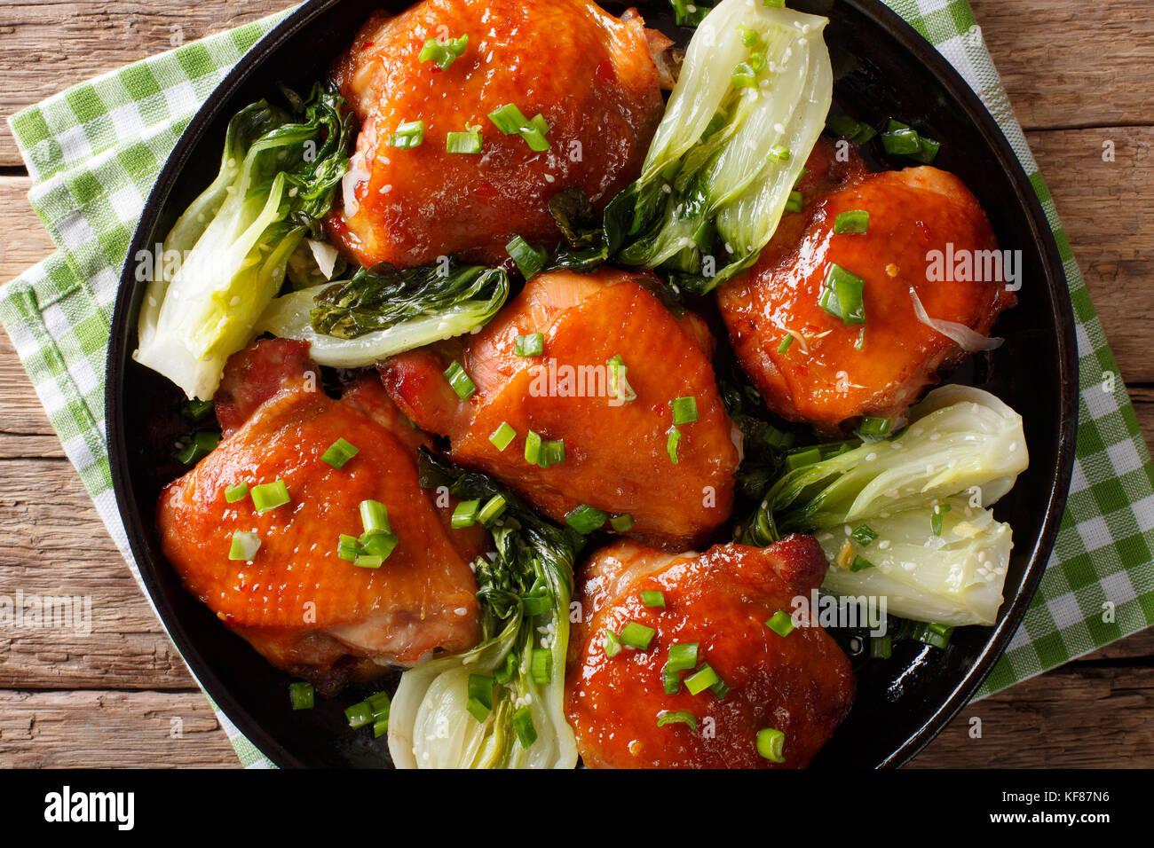 Fried chicken thighs with bok choy and green onions close-up on a plate. Horizontal top view from above - Stock Image