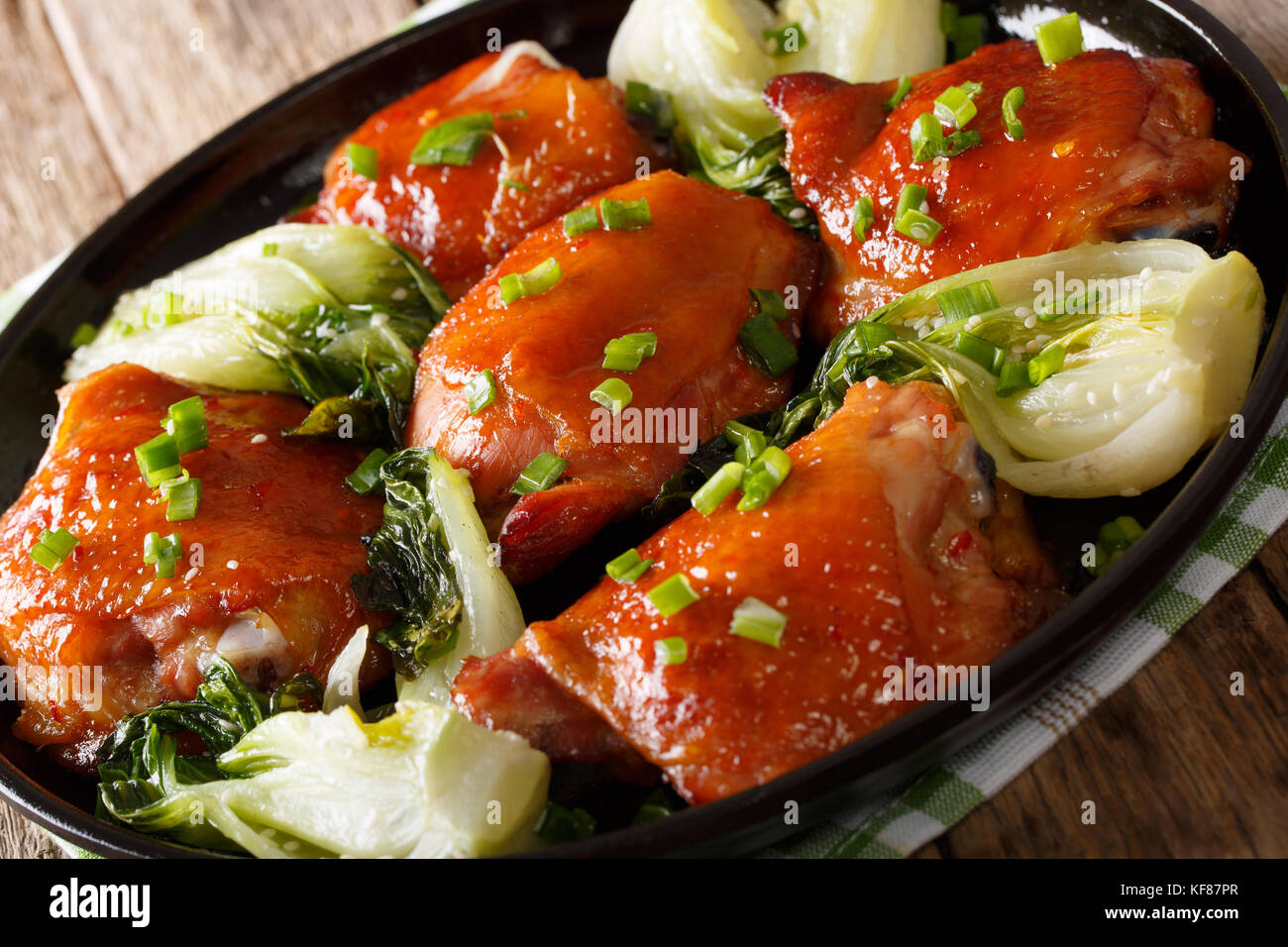 Fried chicken thighs with pak choy, ginger, garlic and green onions closeup on a plate. horizontal - Stock Image