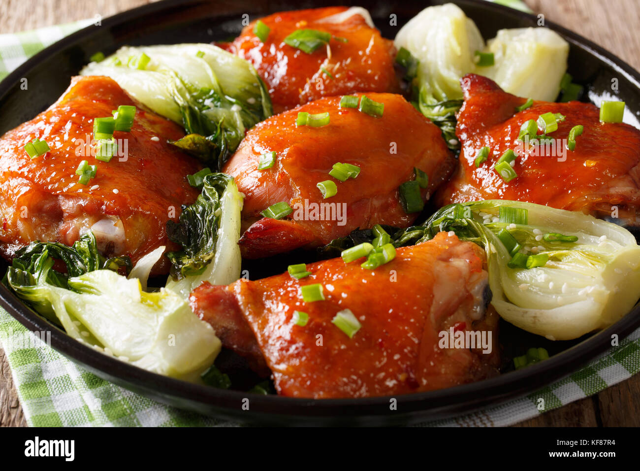 Delicious fried chicken thighs with bok choy and green onions close-up on a plate. horizontal - Stock Image