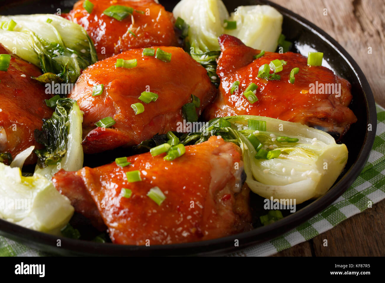 Fried chicken thighs with bok choy and green onions close-up on a plate. horizontal - Stock Image