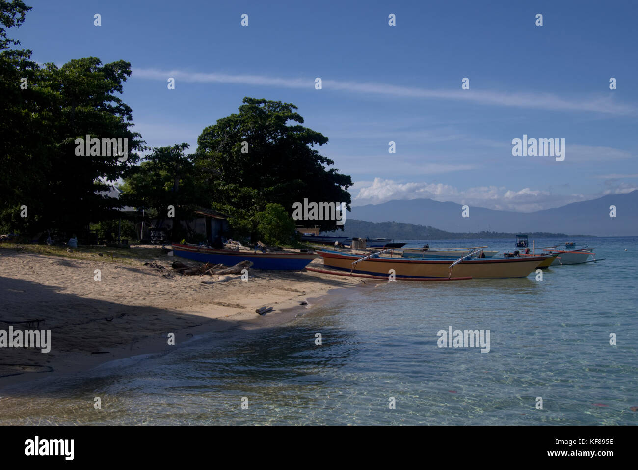 Boats on the beach of Siladen Resort, an island in North Sulawesi, Indonesia - Stock Image