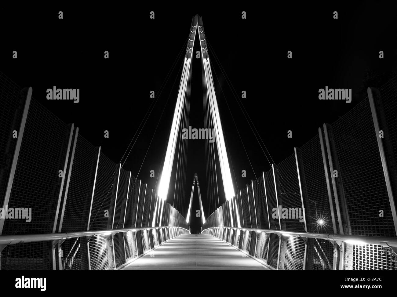 Pedestrian bridge at night. Graphical architectural structure - Stock Image