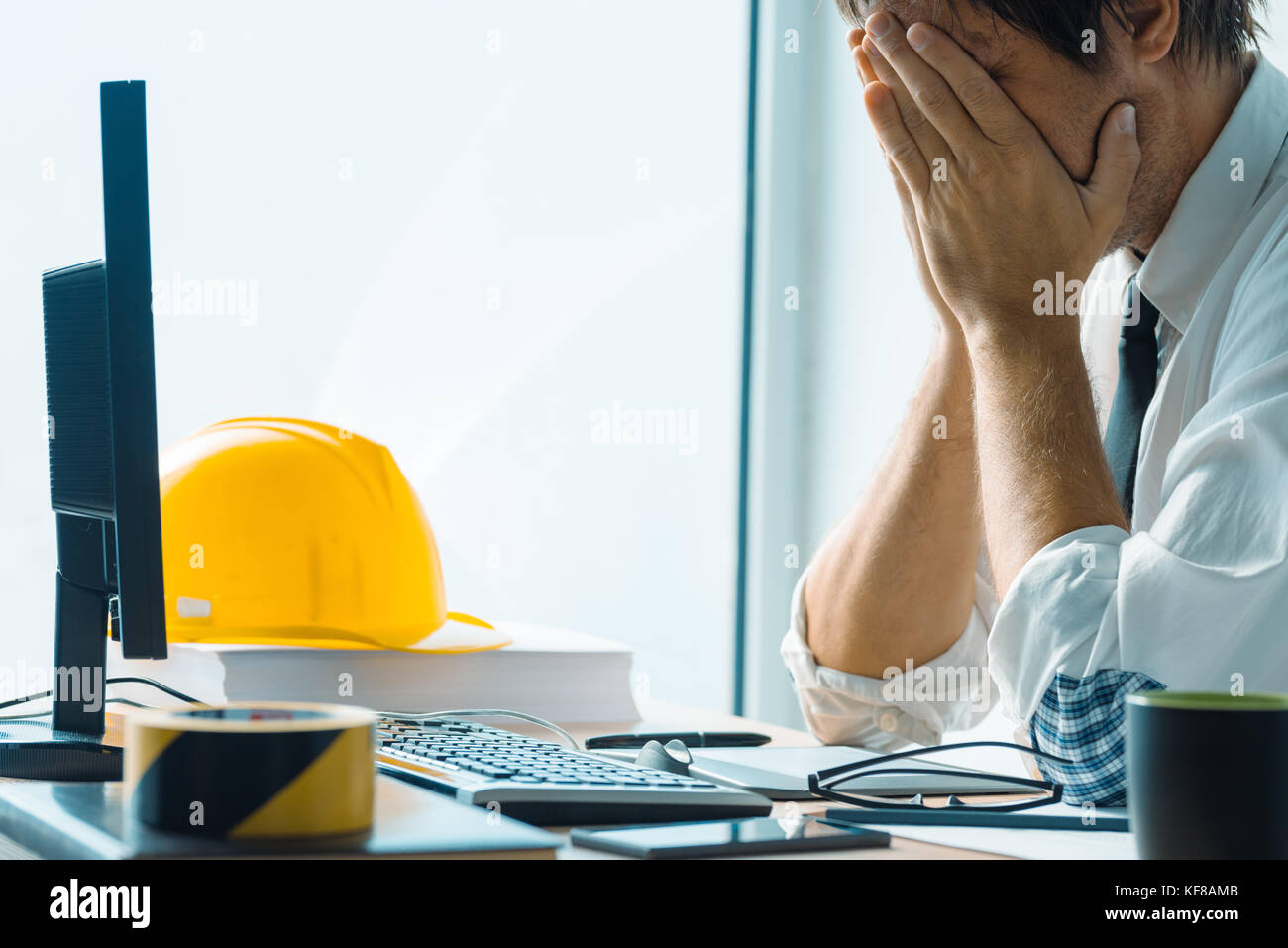 Worried interior design professional working in architecture studio office - Stock Image