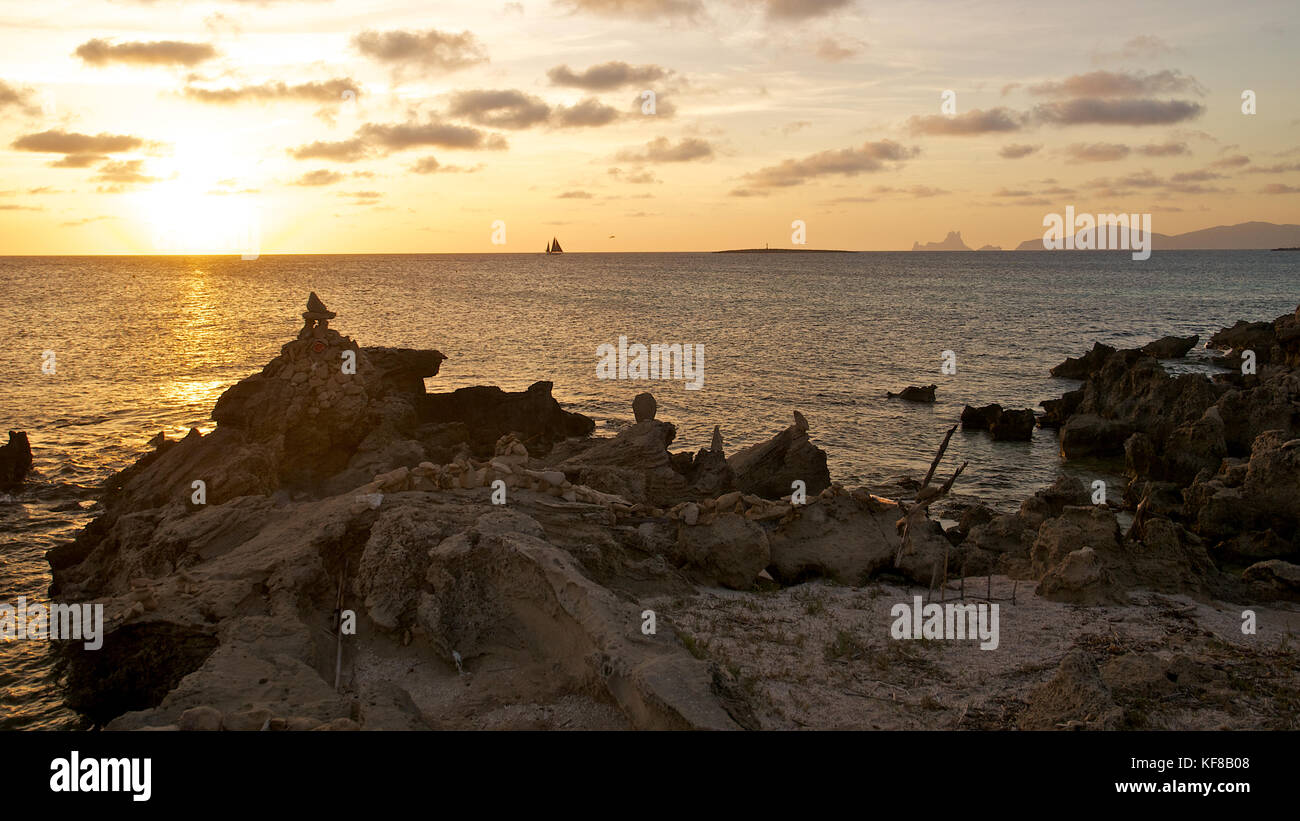 Sunset with stone piles at Ses Illetes beach with Es Vedrá and Ibiza islands in the background from Formentera - Stock Image