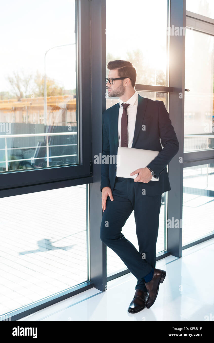 businessman holding laptop in office - Stock Image