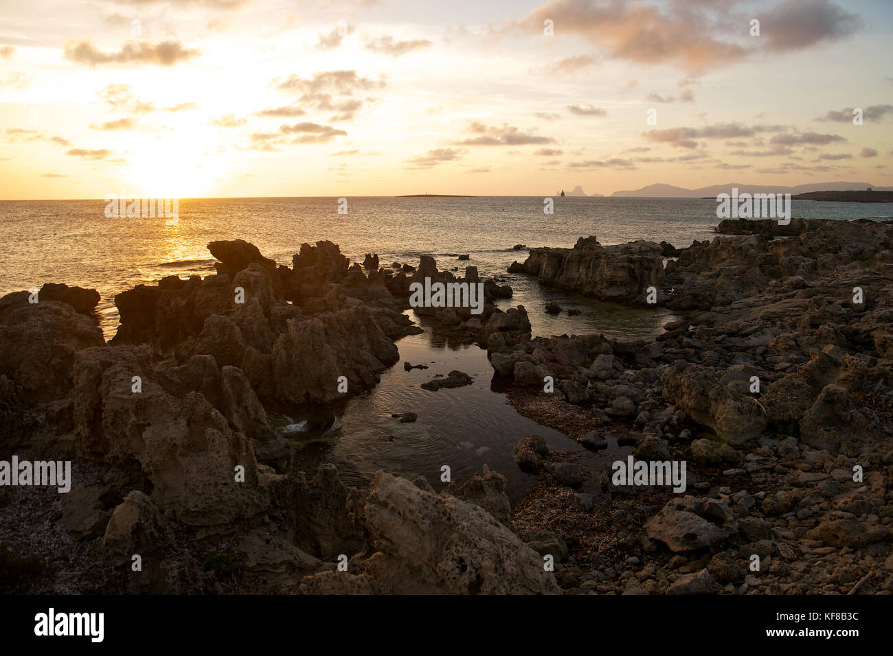 Sunset with seashore rocks near Ses Illetes beach with Es Vedrá and Ibiza islands in the background from Formentera - Stock Image