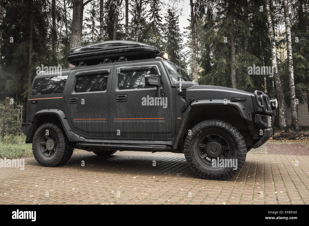 Saint-Petersburg, Russia - October 8, 2017: Black Hummer H2 car stands on rural parking lot in Russian countryside, - Stock Image