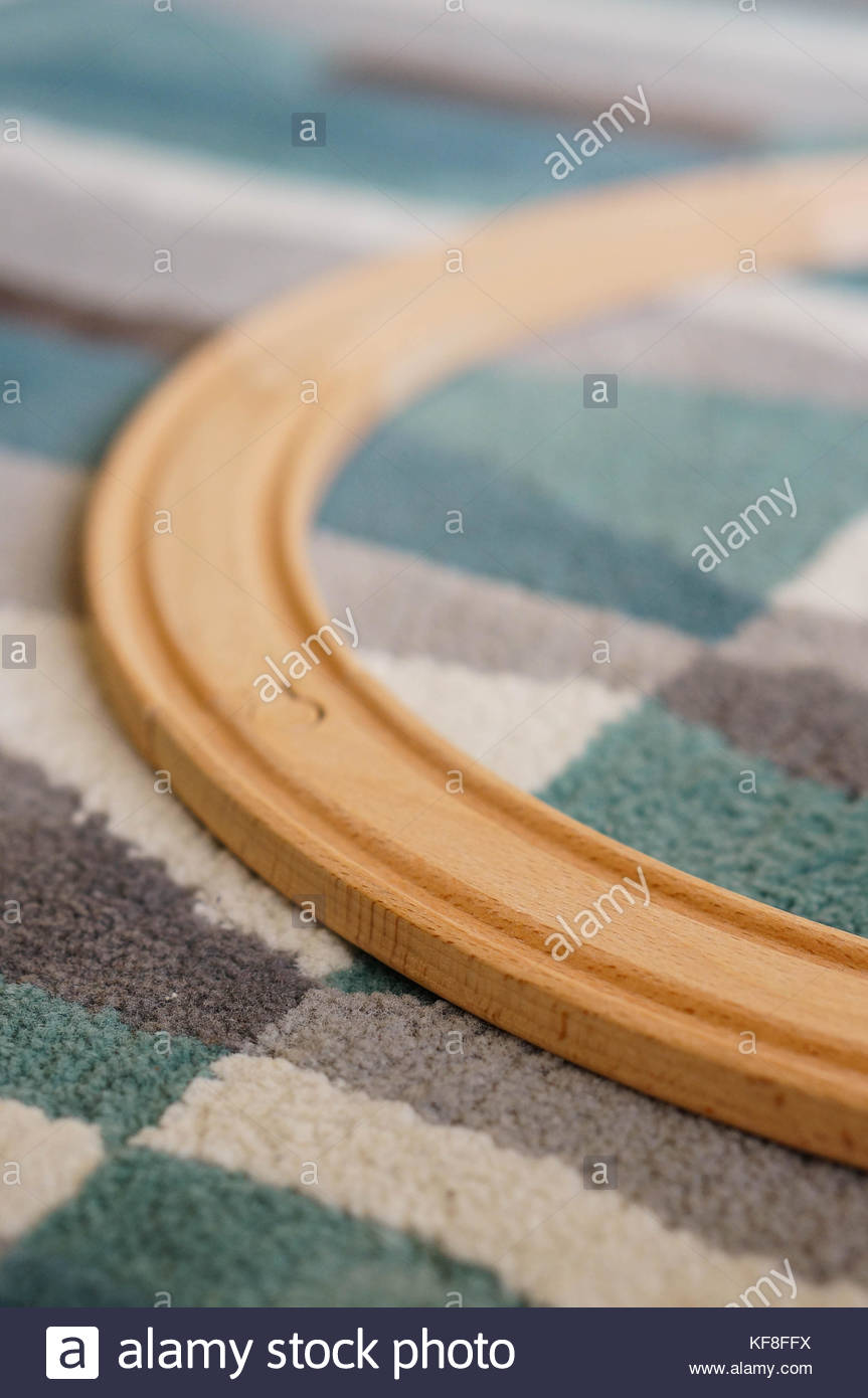 Close up of a wooden toy train track on a carpet Stock Photo