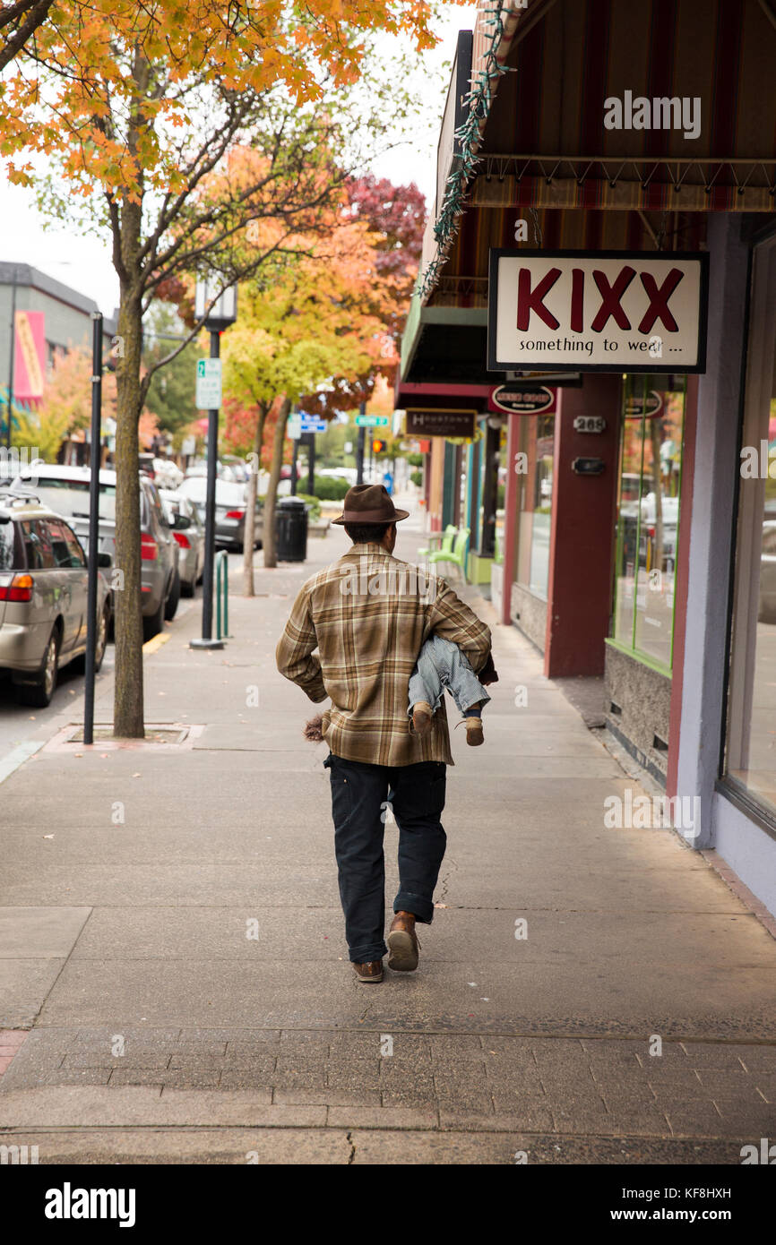 USA, Oregon, Ashland, a man carries his baby under his arm and walks down the sidewalk on East Main street in downtown - Stock Image
