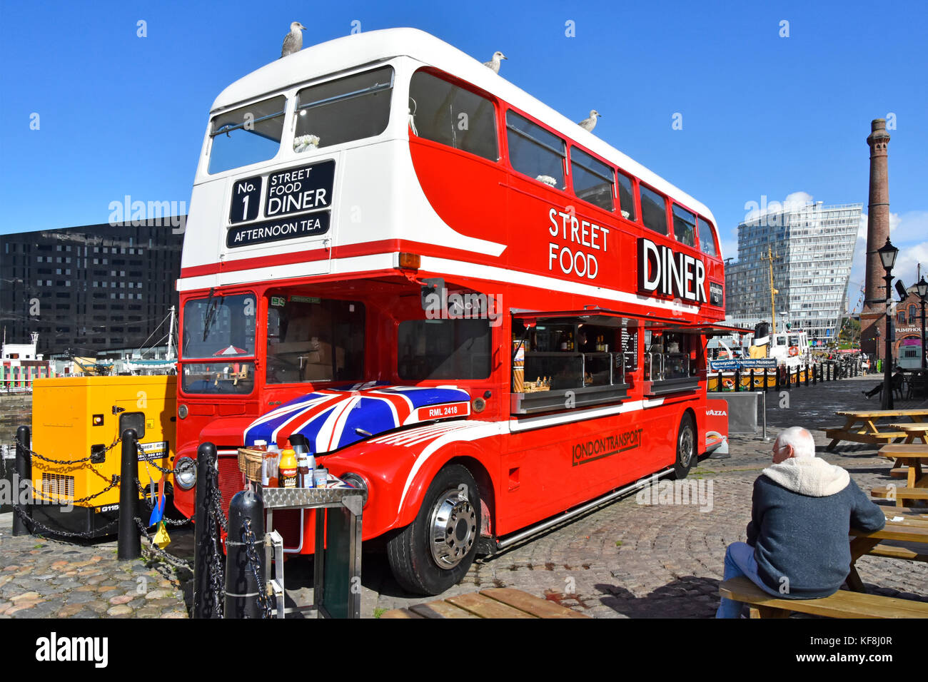 Routemaster bus converted into cafe diner come street food restaurant facility outdoor tables Liverpool albert docks - Stock Image