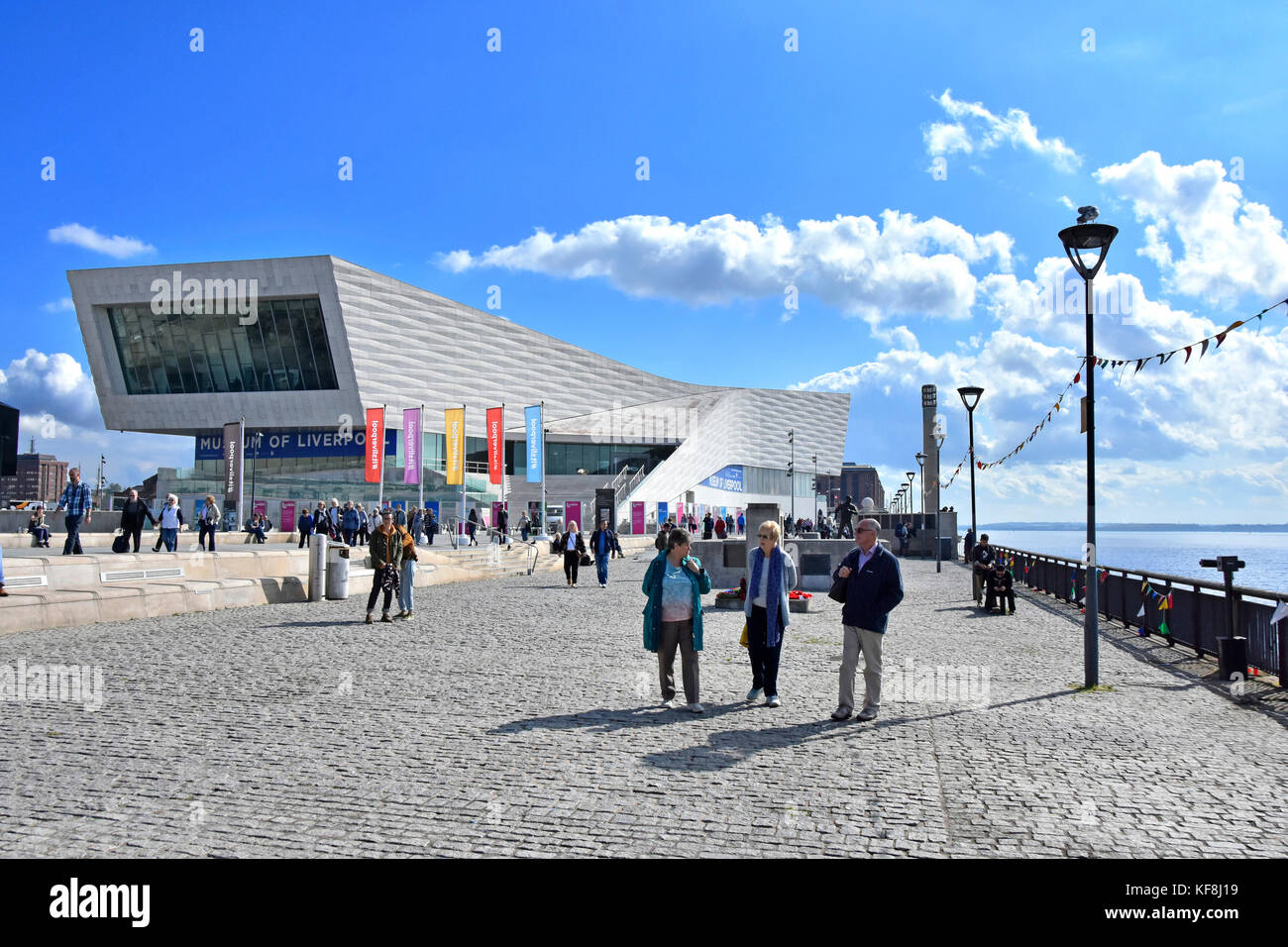 Liverpool Pier Head waterfront 3 M/R tourists nearest camera strolling along the promenade beside River Mersey with - Stock Image
