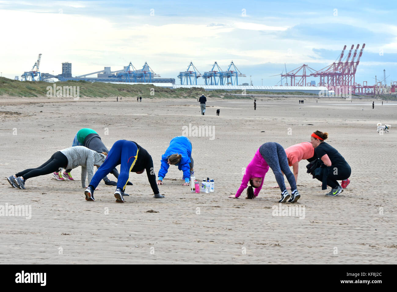 Instructor guiding people taking part in keep fit exercise class on Crosby beach Sefton Liverpool container port - Stock Image