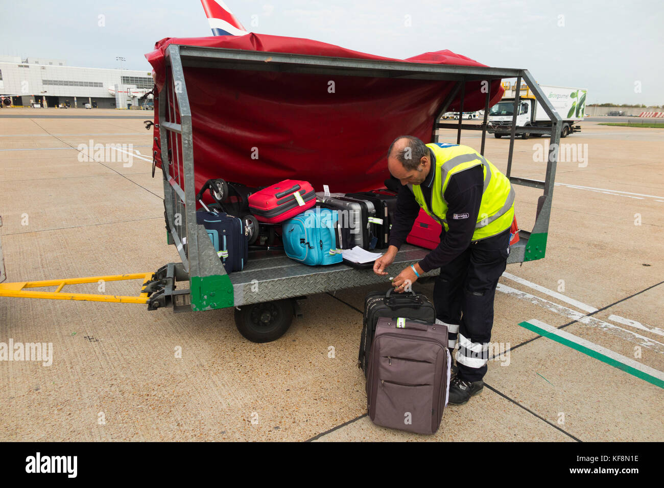 Baggage handlers trolley / truck carrier / vehicle / aircraft loader / container / ground support staff / carrying - Stock Image