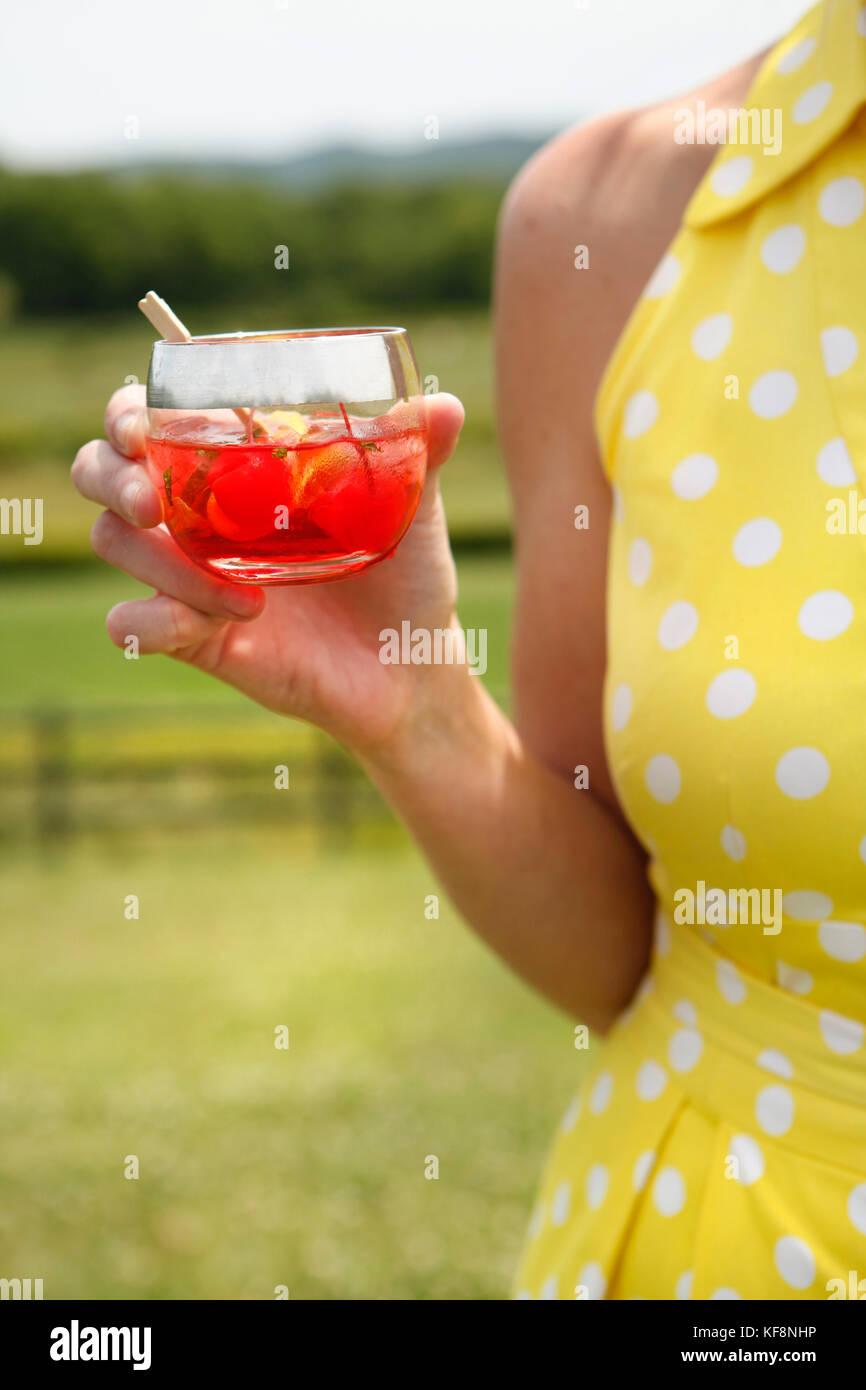 USA, Tennessee, Nashville, Iroquois Steeplechase, woman drinking Moonshine Cherry-Basil Blush - Stock Image
