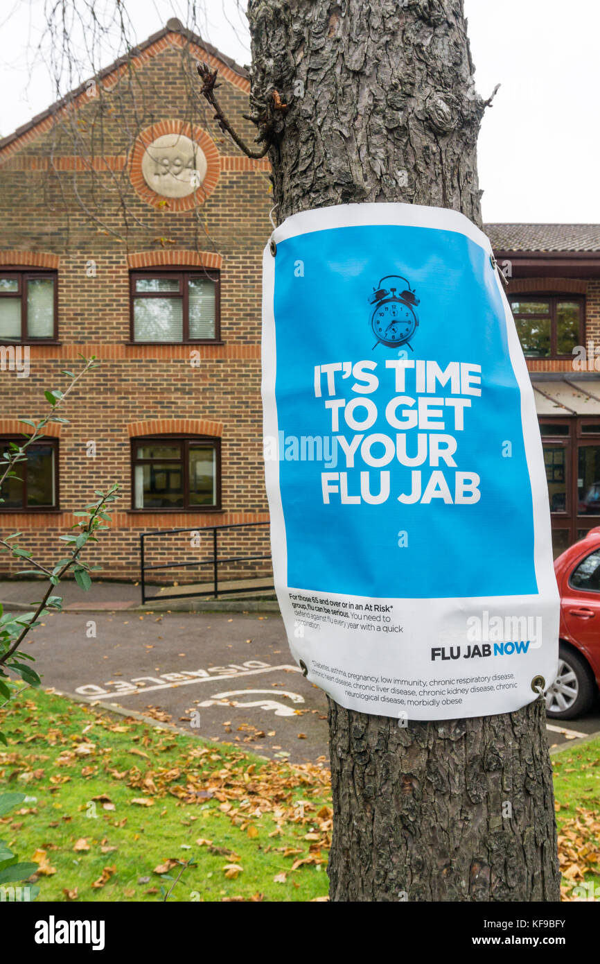 A sign outside a GP or Doctors surgery reads It's Time To Get Your Flu Jab. - Stock Image