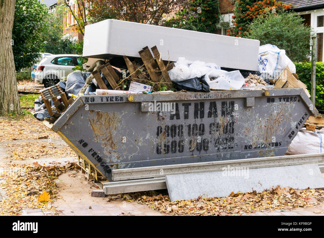 A full waste skip with an old mattress on top of it. - Stock Image